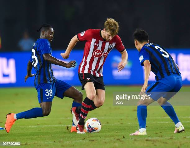 Tian Yinong of Jiangsu Suning and Stuart Armstrong of Southampton compete for the ball during the 2018 Clubs Super Cup match between Southampton FC...