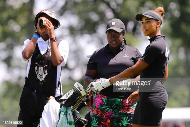Tiana Jones and Amber Kuykendall check the yardage with their caddie on the first hole during the John Shippen National Invitational prior to next...