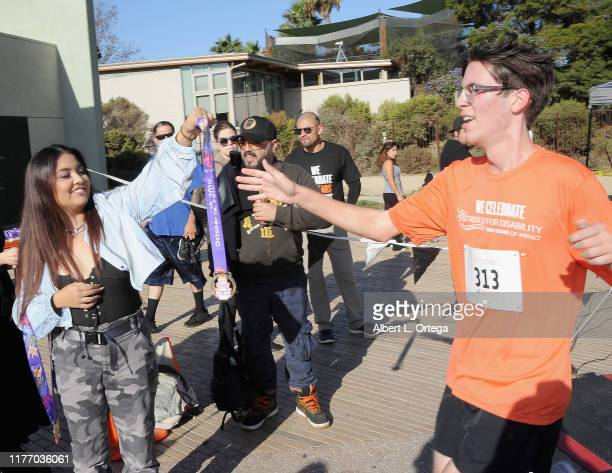 Tiana Kocher passes ouy medals at the 19th Annual Strides For Disability 5K Run held at Shoreline Aquatic Park on October 19 2019 in Long Beach...