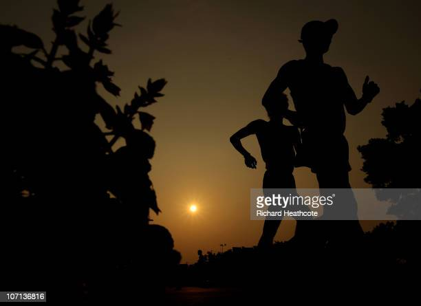 Tianfeng Si of China walks alongside another walker in the men's 50km race walking final at Aoti Main Stadium during day thirteen of the 16th Asian...