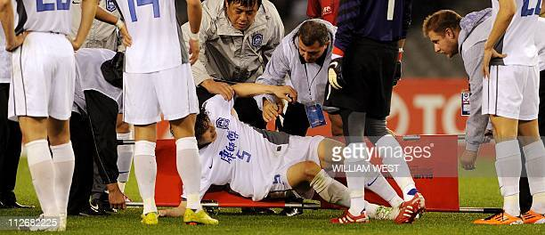 Tianjin Teda's Li Wei Feng is loaded onto a stretcher after been injured against Melbourne Victory in their AFC Champions League match played in...