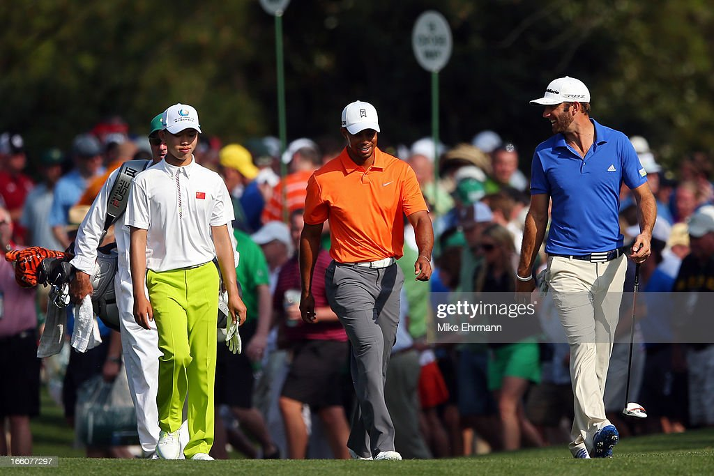 Tianlang Guan of China, Tiger Woods of the United States and Dustin Johnson of the United States walk up the fairway during a practice round prior to the start of the 2013 Masters Tournament at Augusta National Golf Club on April 8, 2013 in Augusta, Georgia.