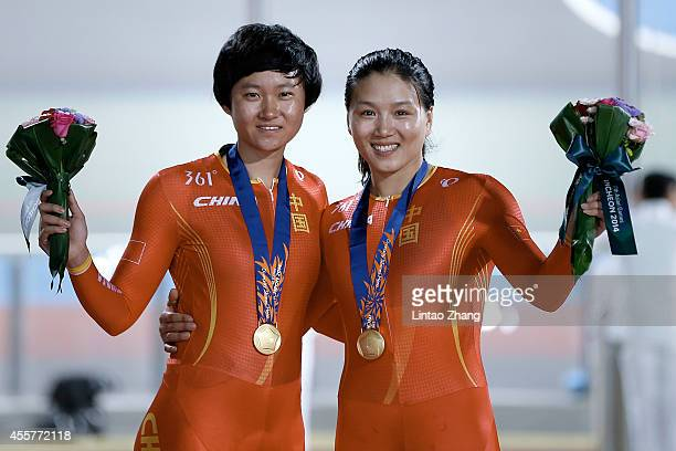 Tianshi zhong and Jinjie Gong of China celebrates with their gold medals after the Cycling Track Women's Team Sprint Finals during the 2014 Asian...
