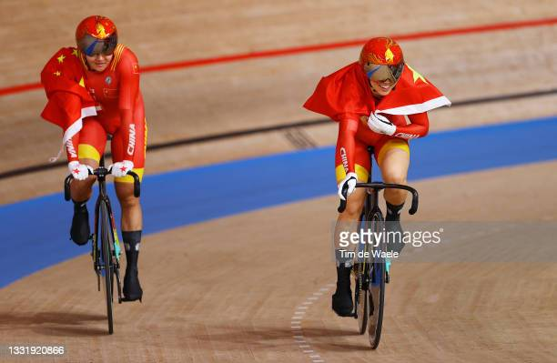 Tianshi Zhong and Shanju Bao of Team China celebrate winning the gold medal while holding the flag of they country after the Women's team sprint...