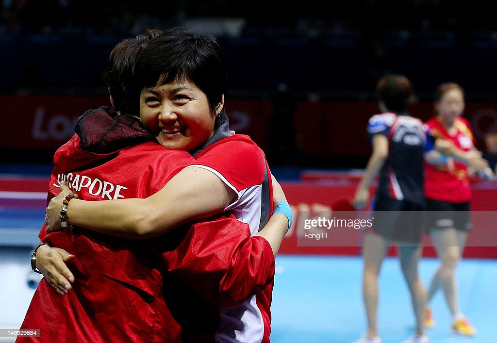 Tianwei Feng (L) of Singapore and head coach Jing Junhong (2nd L) celebrate the 3-1 victory of Yuegu Wang and Jiawei Li of Singapore against Yeseo Dang and Hajung Seok of Korea and on winning the Women's Team Table Tennis bronze medal match on Day 11 of the London 2012 Olympic Games at ExCeL on August 7, 2012 in London, England.