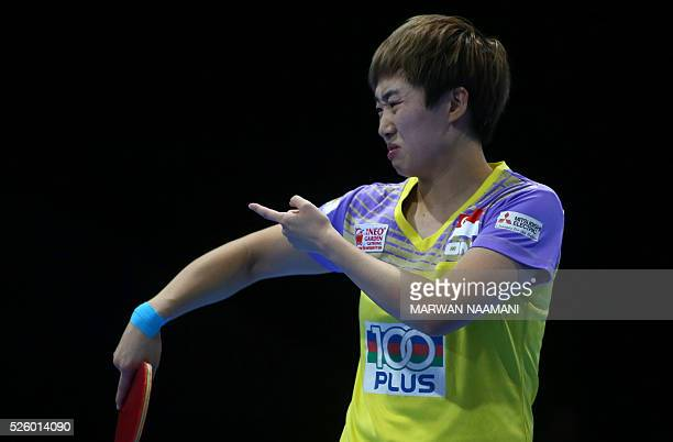 Tianwei Feng of Singapore reacts after a point against Xiaoxia Li of China during their women's singles semi final table tennis match in the ITTF...