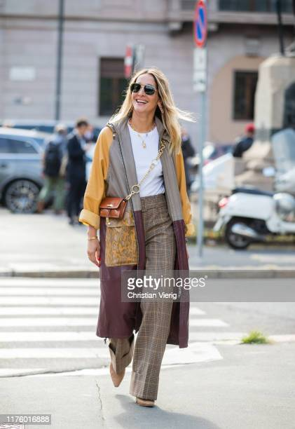 Tiany Kiriloff is seen wearing three tone coat with pockets, checkered pants outside the Tod's show during Milan Fashion Week Spring/Summer 2020 on...