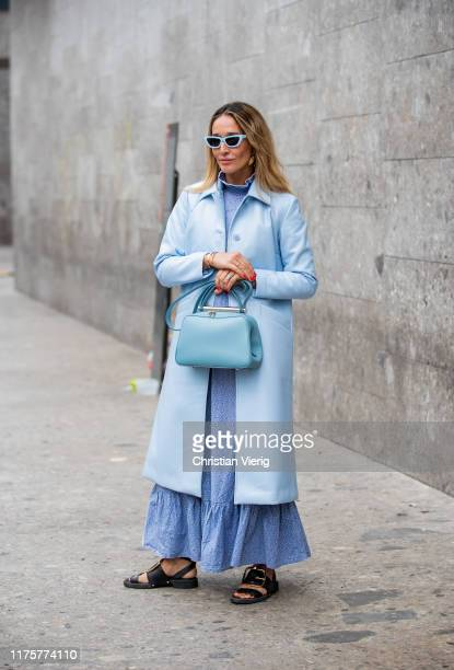 Tiany Kiriloff is seen wearing turquois bag, wool coat, blue dress, sandals outside the Max Mara show during Milan Fashion Week Spring/Summer 2020 on...