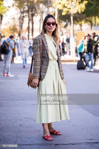 Tiany Kiriloff wearing yellow dress checked blazer Loewe bag and Hermes sandals is seen before the Dries Van Noten show on September 26 2018 in Paris...