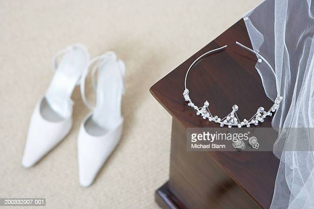 Tiara and earings on cabinet, shoes on floor (focus on foreground)
