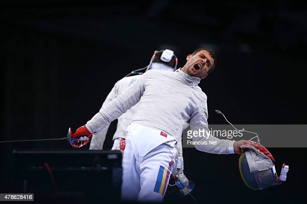 Tiberiu Dolniceanu of Romania celebrates a point against Alberto Pellegrini of Italy during the Men's Fencing Team Sabre Final against Italy on day...