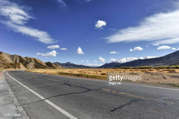 tibet, china: road under blue sky and white clouds - tar stock pictures, royalty-free photos & images