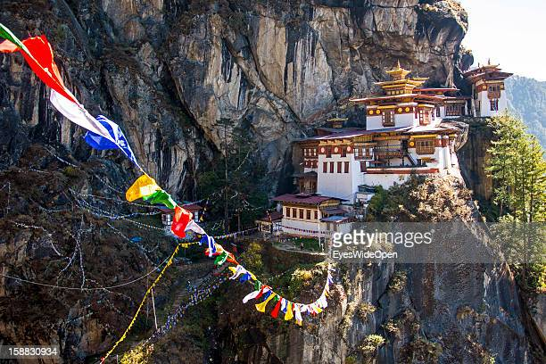 Tibet prayer flags at Paro Taktsang also called Taktsang Palphug Monastery or Tiger `s Nest a famous sacred site and temple complex reachable by a 3...