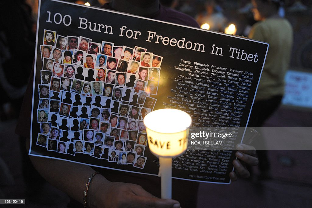 A Tibetan activist holds a candle in front of a poster during protest rally in Hyderabad on March 10, 2013.The protest marked the 54th anniversary of the Tibetan national uprising, the 1959 rebellion against China's rule in Tibet. AFP PHOTO/ Noah SEELAM