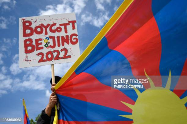 Tibetan activist holds a placard and a Tibetan flag during a protest against Beijing 2022 Winter Olympics in front of the Olympics Museum in Lausanne...