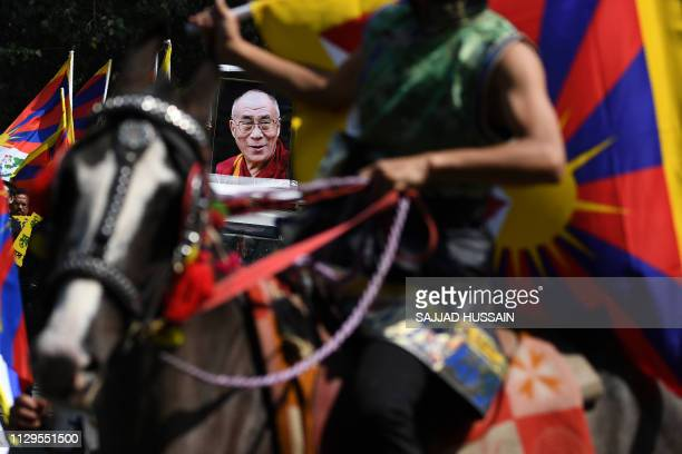 Tibetan activist on a horse is pictured next to a vehicle with the image of Tibetan spiritual leader Dalai Lama during a protest marking the 60th...