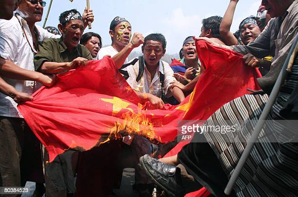 Tibetan activists in exile shout antiChinese slogans as they burn a Chinese flag at the West BengalSikkim interstate border in Rangpo on March 26...