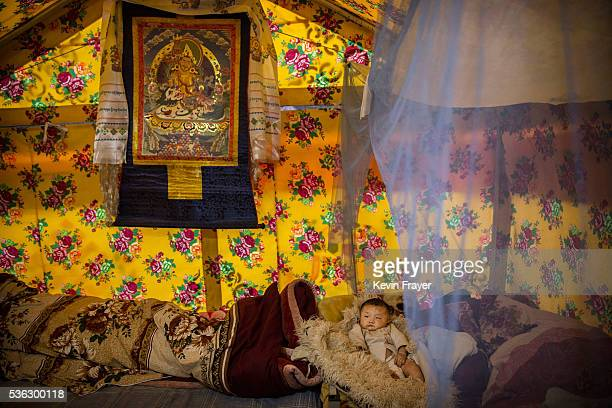 Tibetan baby lays in a tent at a temporary camp for cordycep pickers on May 23 2016 on the Tibetan Plateau near Zadoi in the Yushu Tibetan Autonomous...