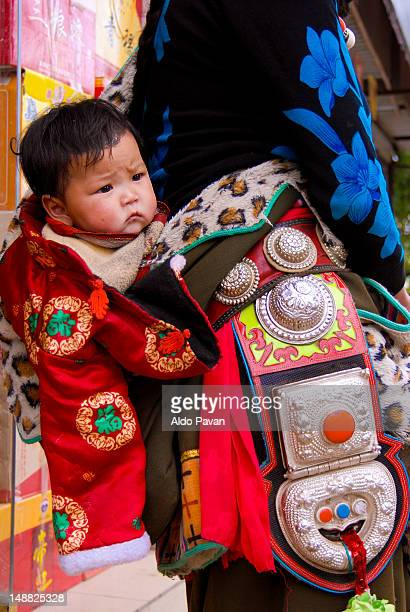 Tibetan boy being carried his mother.