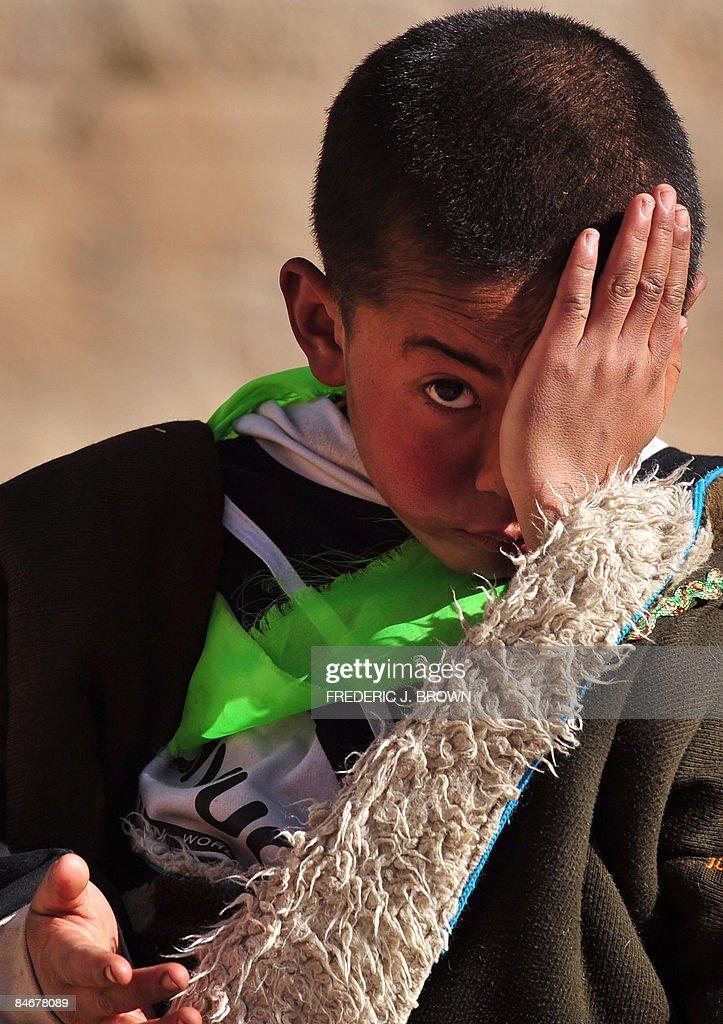 A Tibetan boy covers half his face at th : News Photo