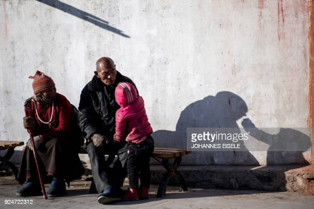 Tibetan boy offers a sweet to his grandfather outside the Labrang Temple during Tibetan New Year celebrations in Labrang on the QinghaiTibet Plateau...
