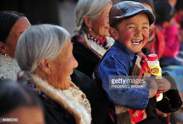 A Tibetan boy smiles after receiving gifts from tourists at the Nyentog Monastery also known as Nianduhu during celebrations for the ongoing Monlam...