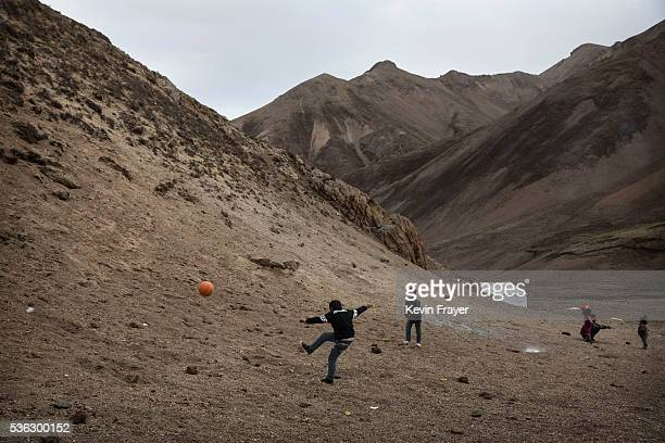 Tibetan boys kick a ball as they play a game at a temporary camp for cordycep pickers on May 23 2016 on the Tibetan Plateau near Zadoi in the Yushu...