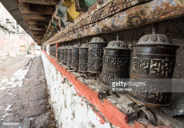 tibetan buddhism prayer wheels in the village of manang along the annapurna circuit trek in the himalayas in nepal - annapurna conservation area stock photos and pictures