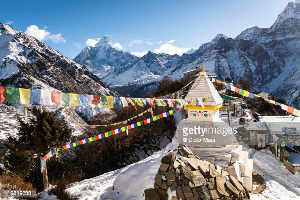tibetan buddhism stupa at the top of the mong la pass in the himalaya with ama dablam peak in nepal. - human settlement stock pictures, royalty-free photos & images