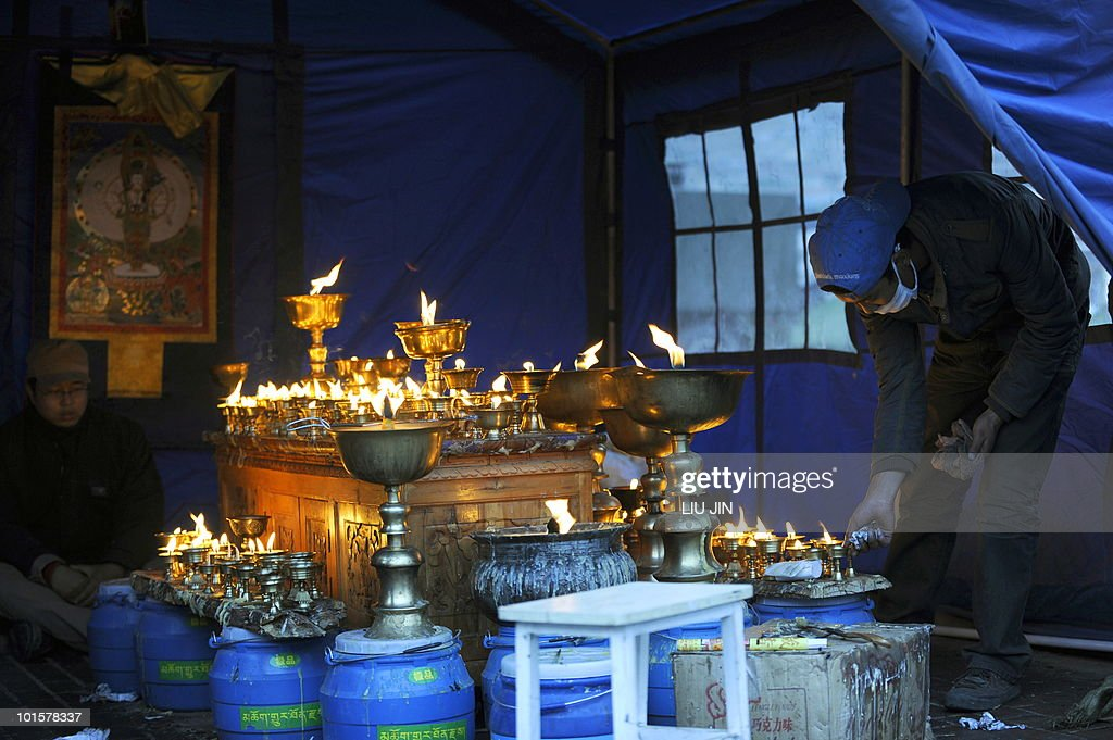 A Tibetan Buddhist believer services the butter fuel lamps for the earthquake victims in Jiegu, Yushu county, in China's northwestern province of Qinghai on April 20, 2010. China declared a national day of mourning for victims of last week's earthquake as rescuers battled altitude sickness and bad weather conditions in the Tibetan disaster zone. AFP PHOTO/ LIU Jin