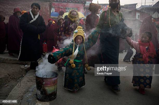 Tibetan Buddhist girl walks through smoke from juniper bruned as a blessing on his way to a morning chanting session at the annual Bliss Dharma...