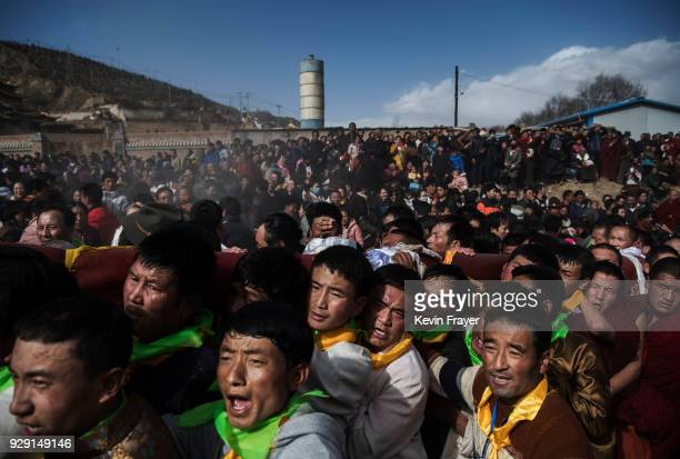 Tibetan Buddhist men carry the rope in front of a rolled up giant thangka before unfurling it on a mountain side at the Rongwo Monastery during...