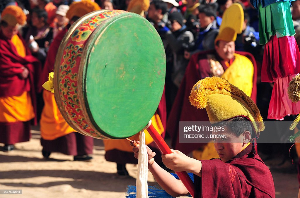 A Tibetan Buddhist monk bangs his drum d : Nachrichtenfoto