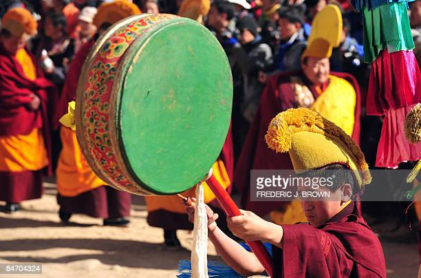 A Tibetan Buddhist monk bangs his drum during a procession leading up to the Sunning of the Buddha when a huge silk thangka showing the image of...