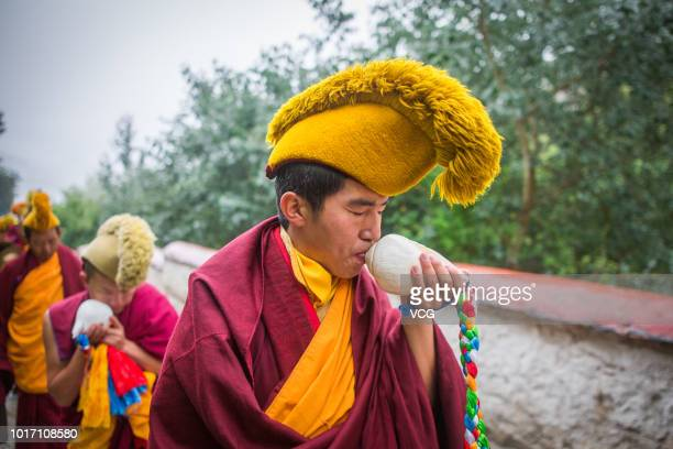Tibetan Buddhist monk blows a conch on the first day of the traditional Sho Dun Festival at Drepung Monastery on August 11 2018 in Lhasa Tibet...