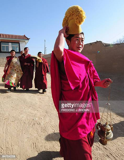 A Tibetan Buddhist monk carries an incense urn at the Nyentog Monastery also known as Nianduhu during celebrations for the ongoing Monlam or Great...