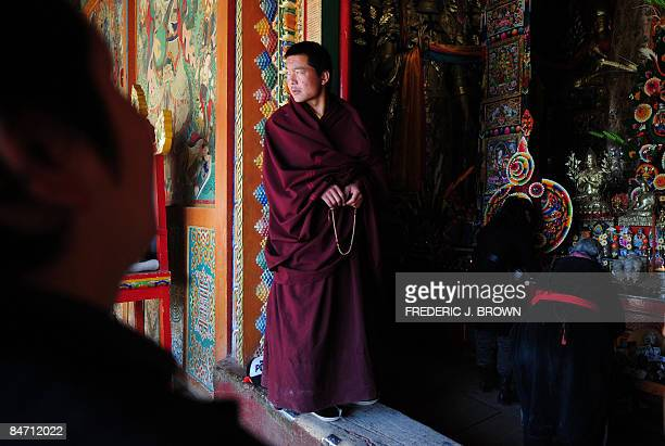 A Tibetan Buddhist monk looks on as people people pray during celebrations for Monlam or the Great Prayer Festival at the Nyentog Monastery also...