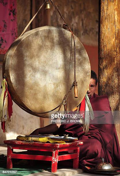 A Tibetan Buddhist monk looks on while reading a scripture ringing a bell and banging a drum during ongoing celebrations for Monlam or the Great...