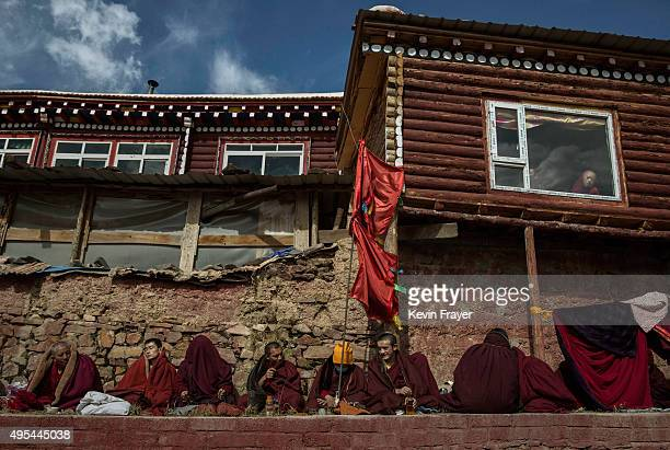 Tibetan Buddhist monk looks out the window of a dweilling as others sit during a morning chanting session as part of the annual Bliss Dharma Assembly...