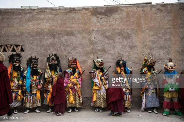 Tibetan Buddhist Monk of the Gelug or Yellow Hat school wear masks as as they lineup in a procession following a Cham dance at the Rongwo Monastery...