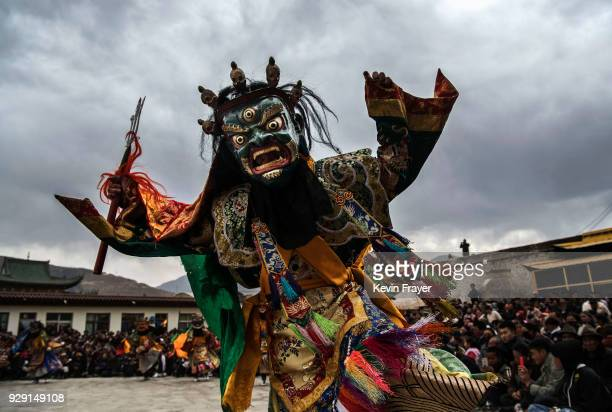 Tibetan Buddhist Monk of the Gelug or Yellow Hat school wears a mask as he dances during a Cham dance at the Rongwo Monastery during Monlam or the...