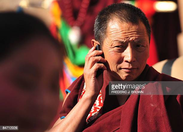 A Tibetan Buddhist monk on his mobile phone as people gather during celebrations for Monlam or the Great Prayer Festival at the Nyentog Monastery...