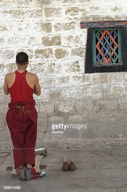 Tibetan buddhist monk prostrating in front of a wall of Jokhang Temple Lhasa Tibet China August 2004