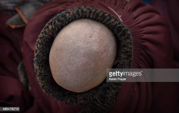 A Tibetan Buddhist monk tries to keep warm in subzero temperatures before a chanting session at the annual Bliss Dharma Assembly at the Larung Wuming...