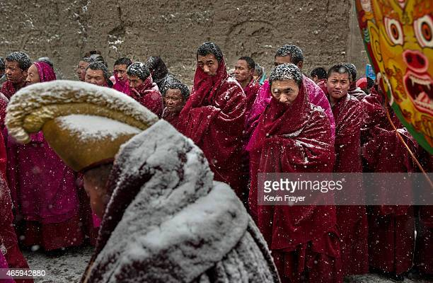 Tibetan Buddhist monks are covered in snow as they take part in a procession during Monlam or the Great Prayer rituals on March 4 2015 at the Labrang...
