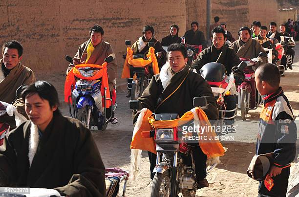 Tibetan Buddhist monks arrive riding motorcycles during morning activities leading up to the Sunning of the Buddha when a huge silk thangka showing...