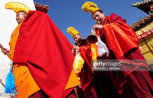 Tibetan Buddhist monks blow horns during celebrations for the ongoing Monlam or Great Prayer Festival at the Nyentog Monastery also known as Nianduhu...
