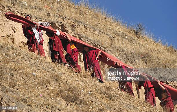 Tibetan Buddhist monks carry a huge thanka showing the image of Sakyamuni the founder of Buddhism up a hillside to be unfurled for a few minutes...
