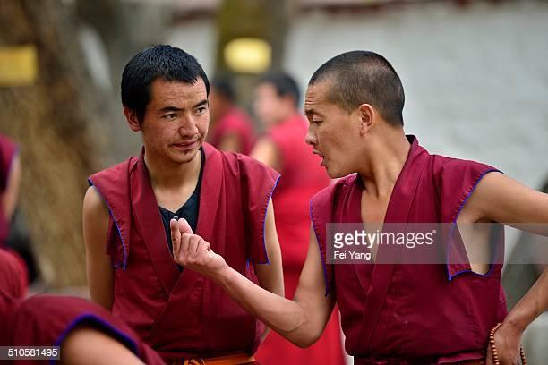 Tibetan Buddhist monks debate scripture in the courtyard of the Sera Monastery