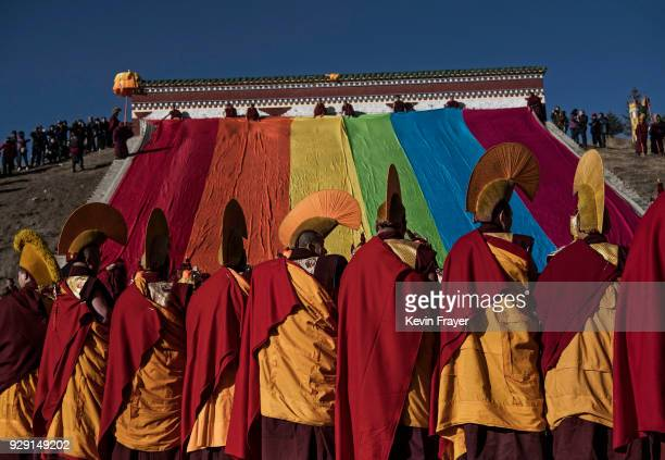 Tibetan Buddhist Monks of the Gelu or Yellow Hat school unfurl a large thangka of the Buddha during Monlam or the Great Prayer on February 28 2018 in...